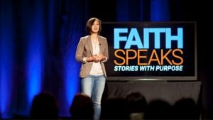 "Woman speaking on stage with ""Faith Speaks"" in the background"