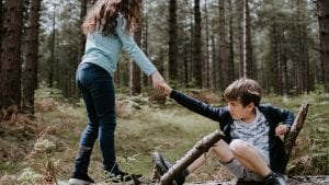 Kids playing on a log and girl is helping boy stand.