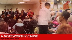 Members of orchestra standing in front of nursing home residents holding their instruments and smiling crossfaded with boy shaking hands with smiling nursing home residents.