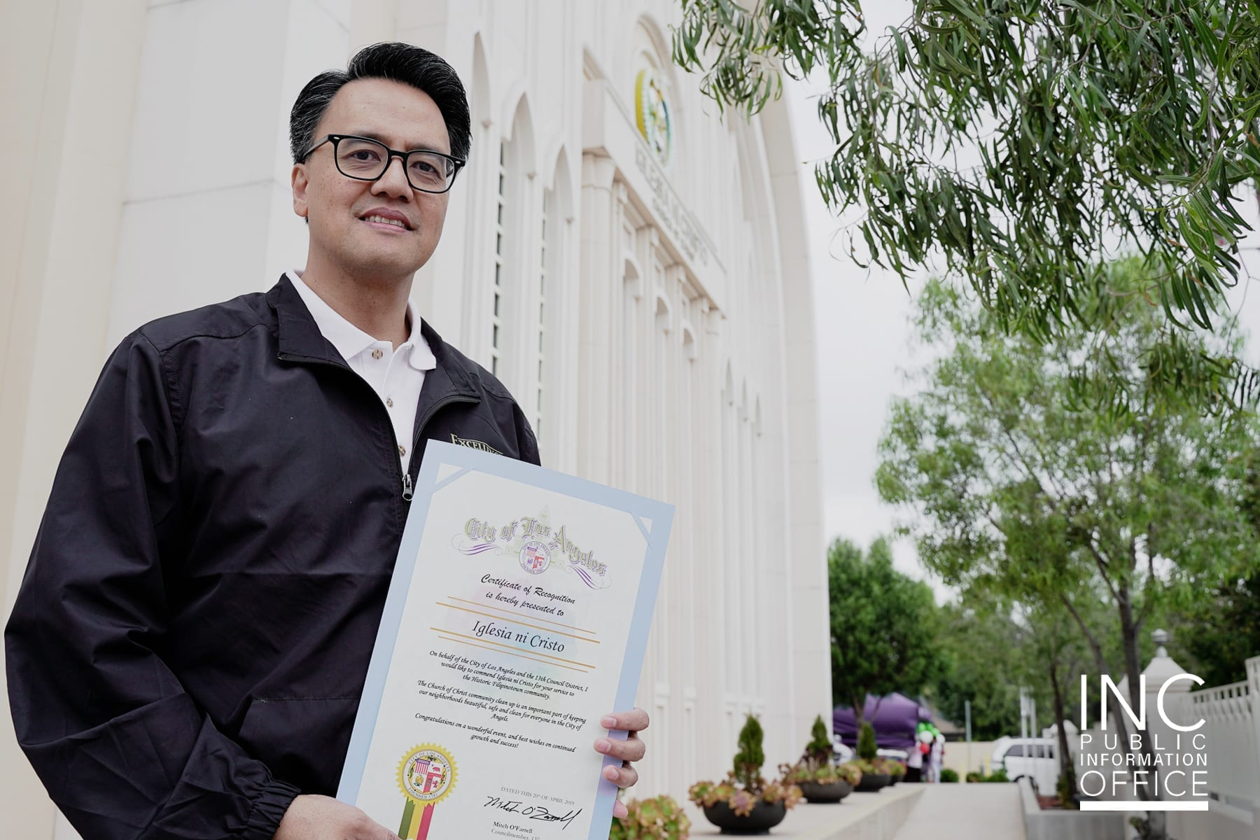 man smiling at camera with certificate in front of house of worship chapel