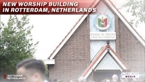Front exterior of chapel with heads in the foreground with text overlay reading: New Worship Building Dedicated in Rotterdam