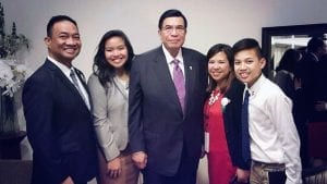 A man with his family stand beside the Executive Minister of the Church Of Christ