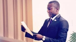 Profile of a man wearing a suit reading a letter.