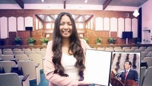 A woman holding a letter and photo from the Executive Minister inside a chapel sanctuary of the Church Of Christ.
