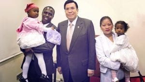 A mom, dad, and their two daughters smile while standing with the Executive Minister.