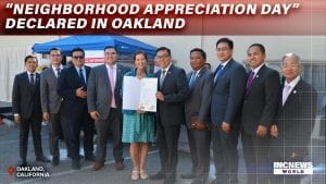 A group of men and the mayor pose with an official document.
