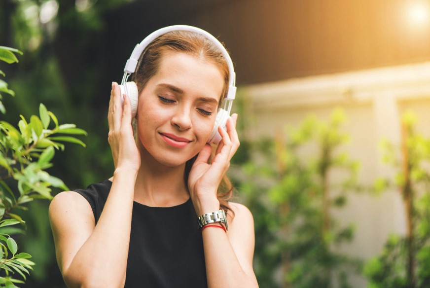 Woman smiling with her eyes closed with hands on her headphones