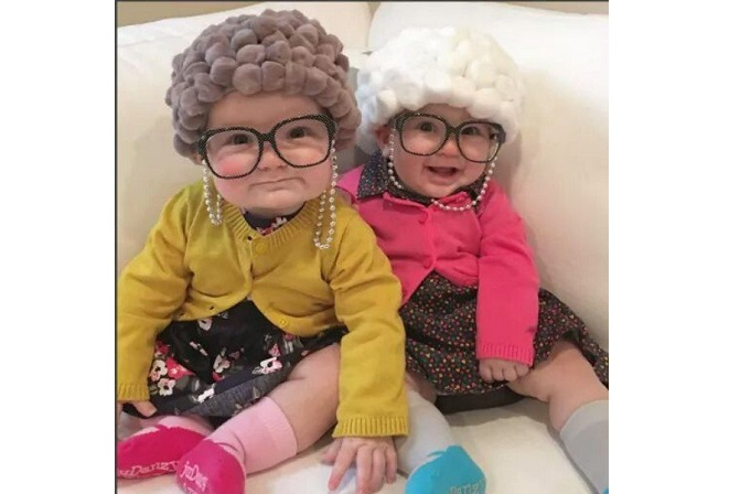 Two kids on a couch dressed up as old people.