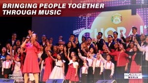 A Choral group comprised of different age groups sing on stage together.