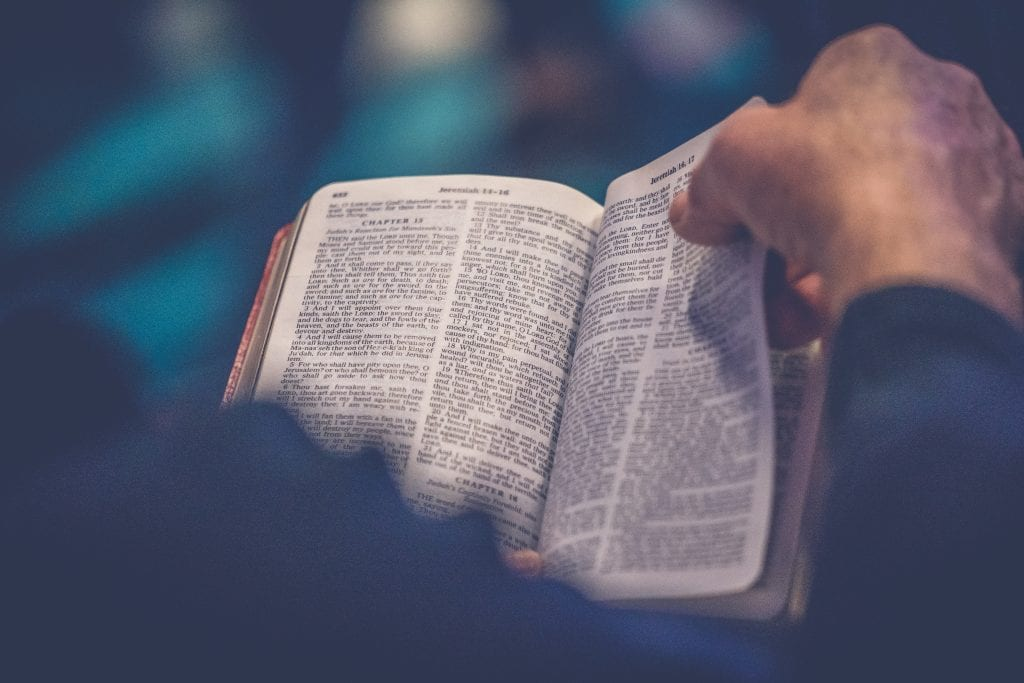Man's hands reading the Bible