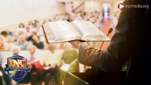 Back of man holding a Bible in front a church congregation