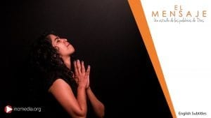 A prayerful spanish lady facing towards the sky to the right, with her eyes closed, and with her hands placed firmly together in the darkness. El Mensaje logo shown on top right of image.