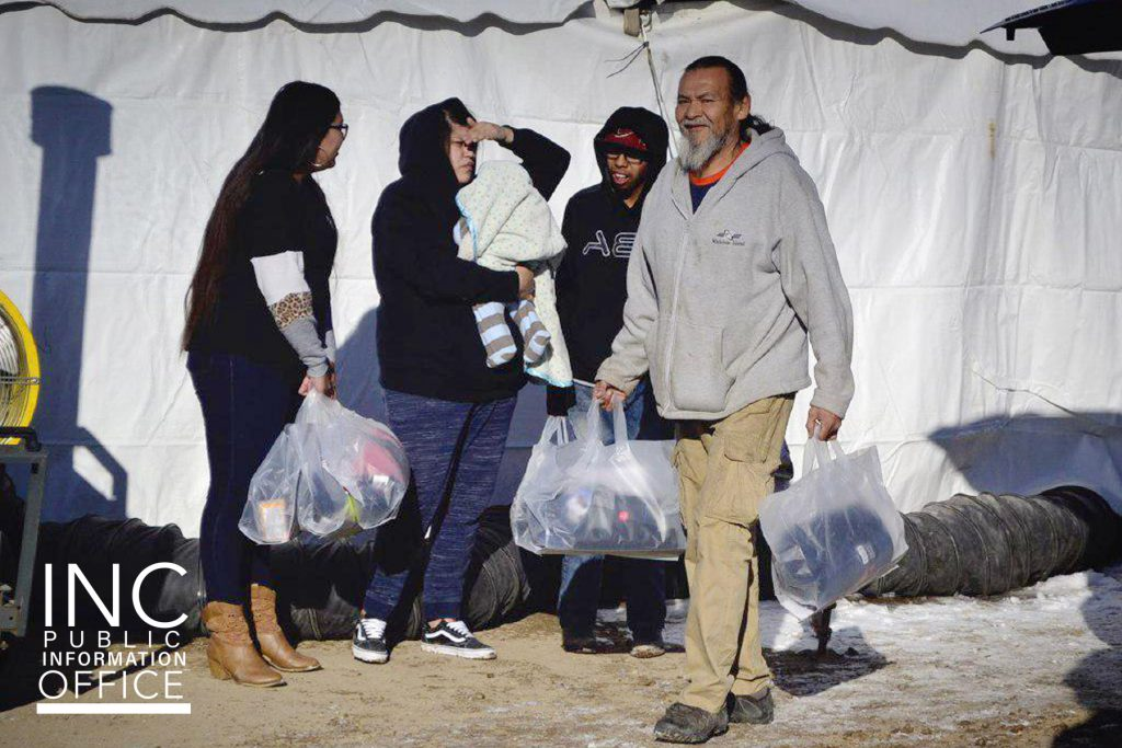 man carrying winter relief packages leaves the event tent