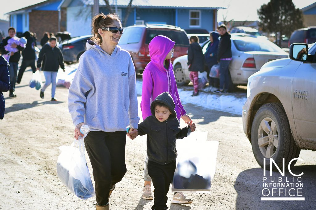 woman and children walking in the street carrying winter relief packages