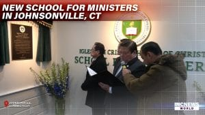 Three men officiate the inauguration of a new school, with the official plaque and logo on the walls.