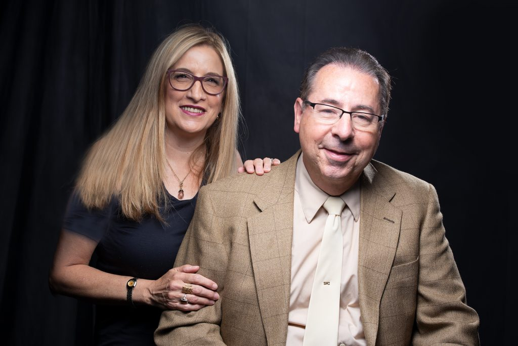 A smiling couple against a black background
