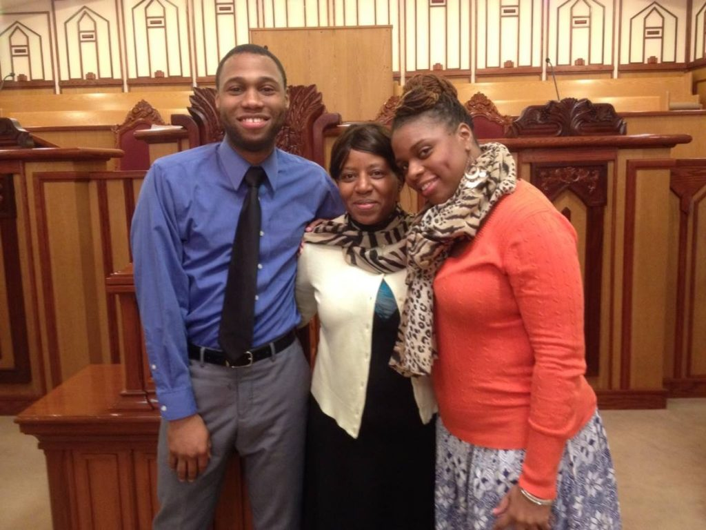 Young man with mom and sister in front of a podium
