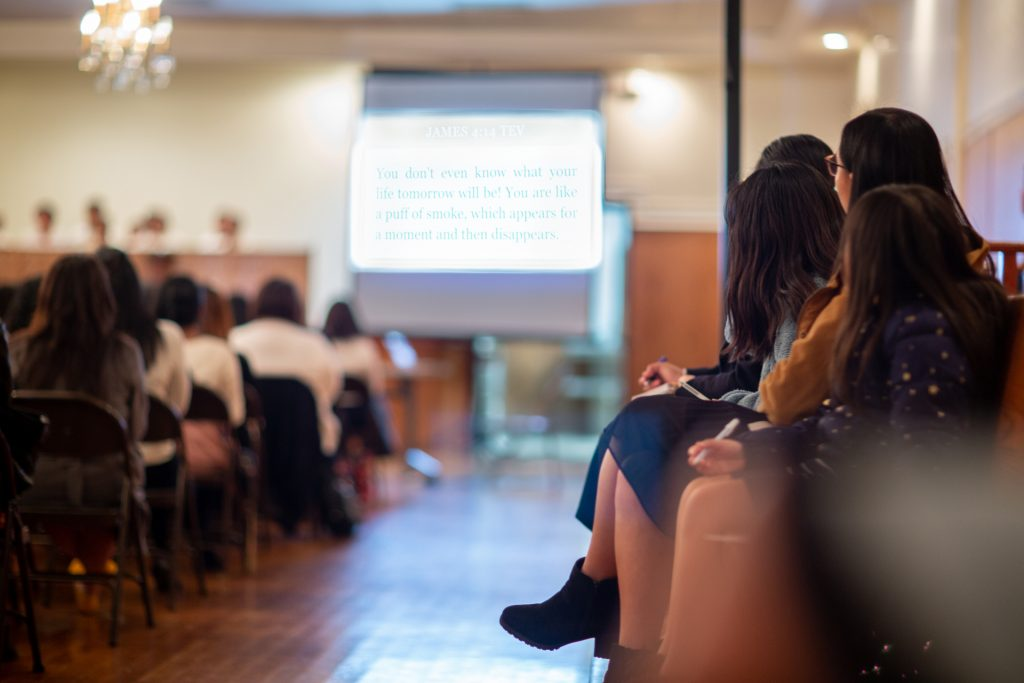 A worship service setting with a group of people looking at a screen holding a pen and paper.