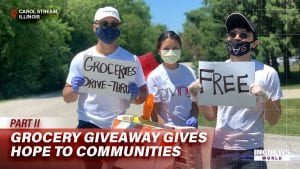 Volunteers with masks hold signs for a grocery bag event