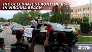 A caravan of cheerleaders pass by as a crowd waves.
