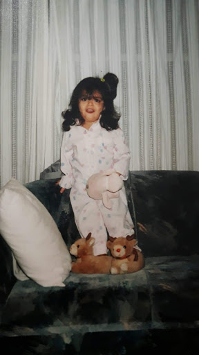 Young Mariela in her pajamas standing on a couch