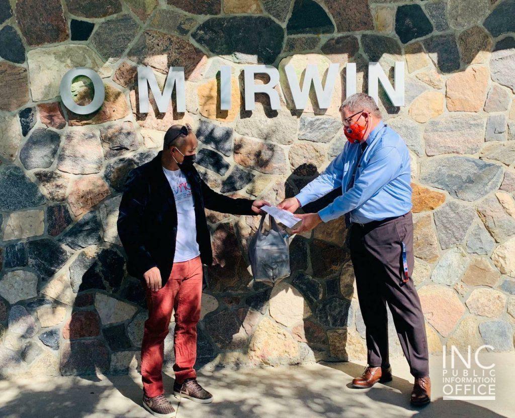 O.M. Ir win School Principal Arron Kohlman (right) accepts 450 disposable face masks from a Church Of Christ volunteer.