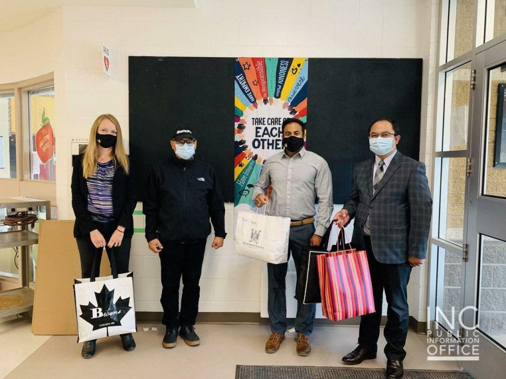 Vice Principal Dena Arnold (far left) from the Ecole Leila North Community School accepts 400 re-usable face masks from the Church Of Christ (Iglesia Ni Cristo) Aid To Humanity Project.