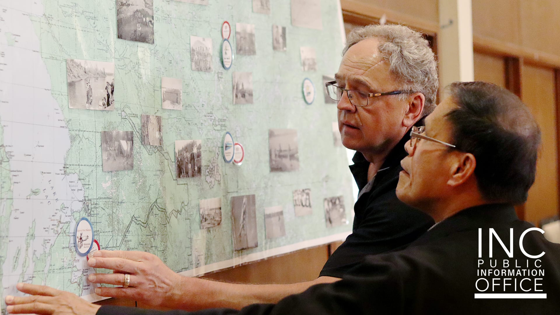 Two men standing in front of a map of the indigenous populations of Manitoba