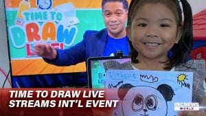 A girl smiles and holds up a drawing, behind her, a man is on the TV screen.