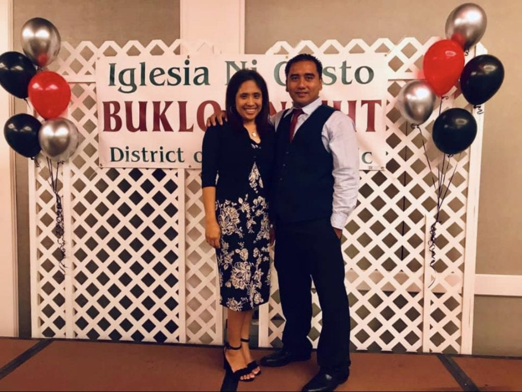 Couple smiling standing in front of an Iglesia Ni Cristo Buklod banner