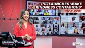 A female show host smiles and stands in front of TV screens with people connected through video conference.
