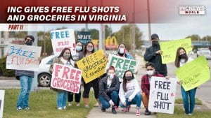 "A group of young adults with masks hold up signs for ""free flu shots"" and ""free groceries"""