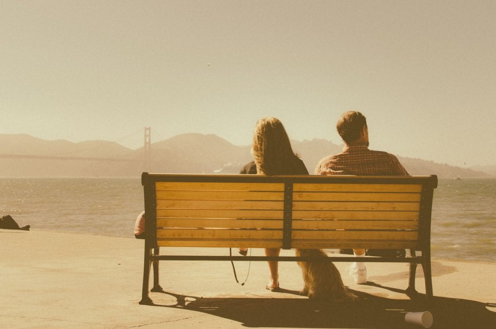 Couple sitting on a bench looking out to Golden Gate Bridge