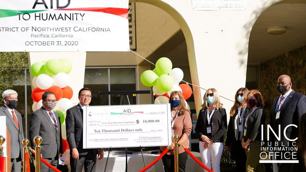 Representatives of all organizations gather around a large format donation check for the amount of $10,000