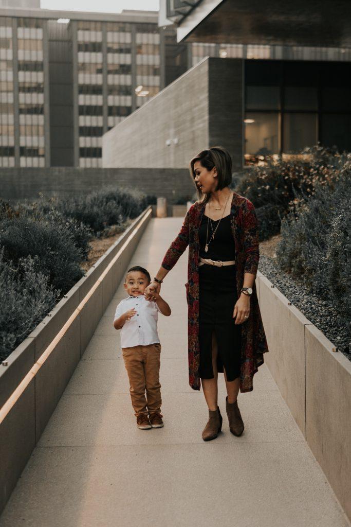 Son pulling back as mom walks forward.