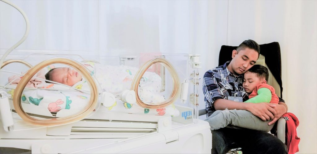 A baby in NICU while dad and son sleep next to bed.