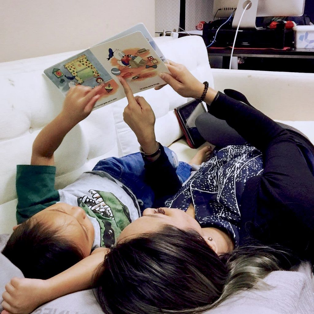 Mom and son reading a book lying down on couch.