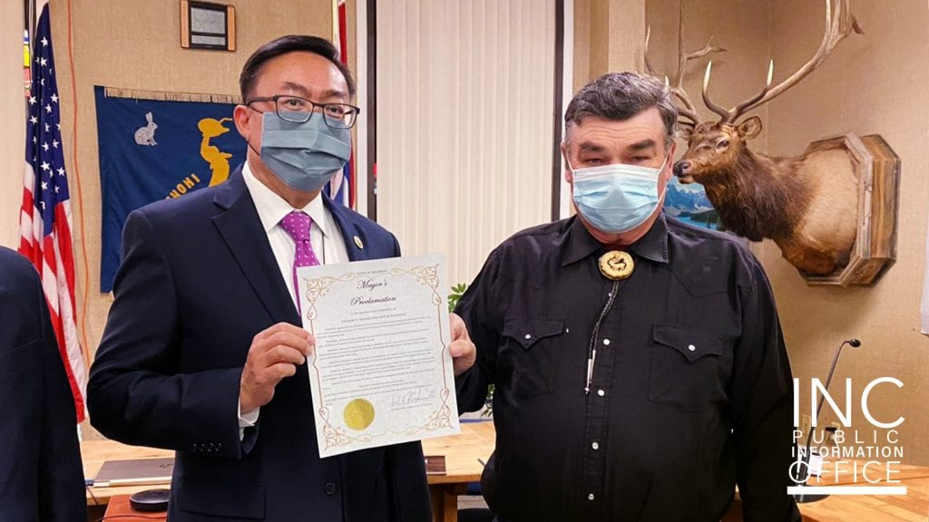 Two men holding a certificate in a town hall meeting