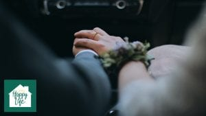 A newly married husband and wife sitting in a car and holding hands.