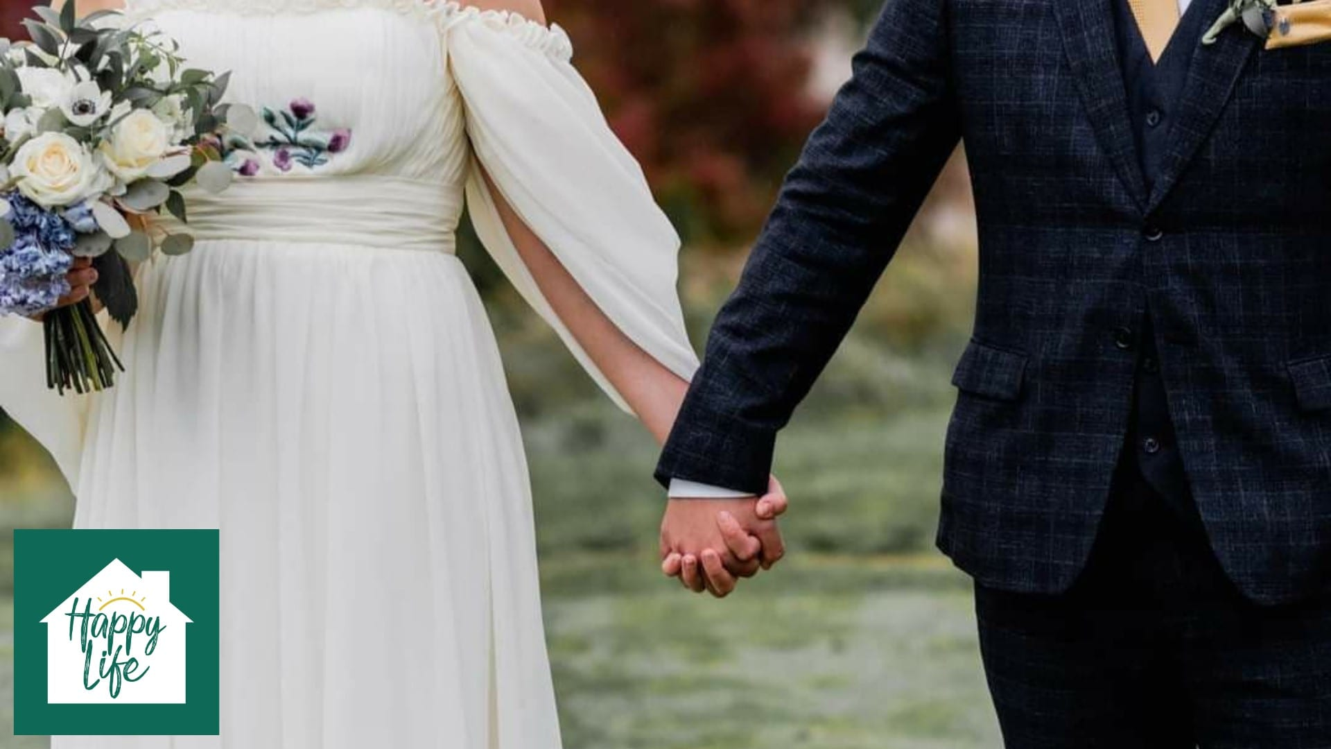 A newly married husband and wife hold hands as they stand side by side.