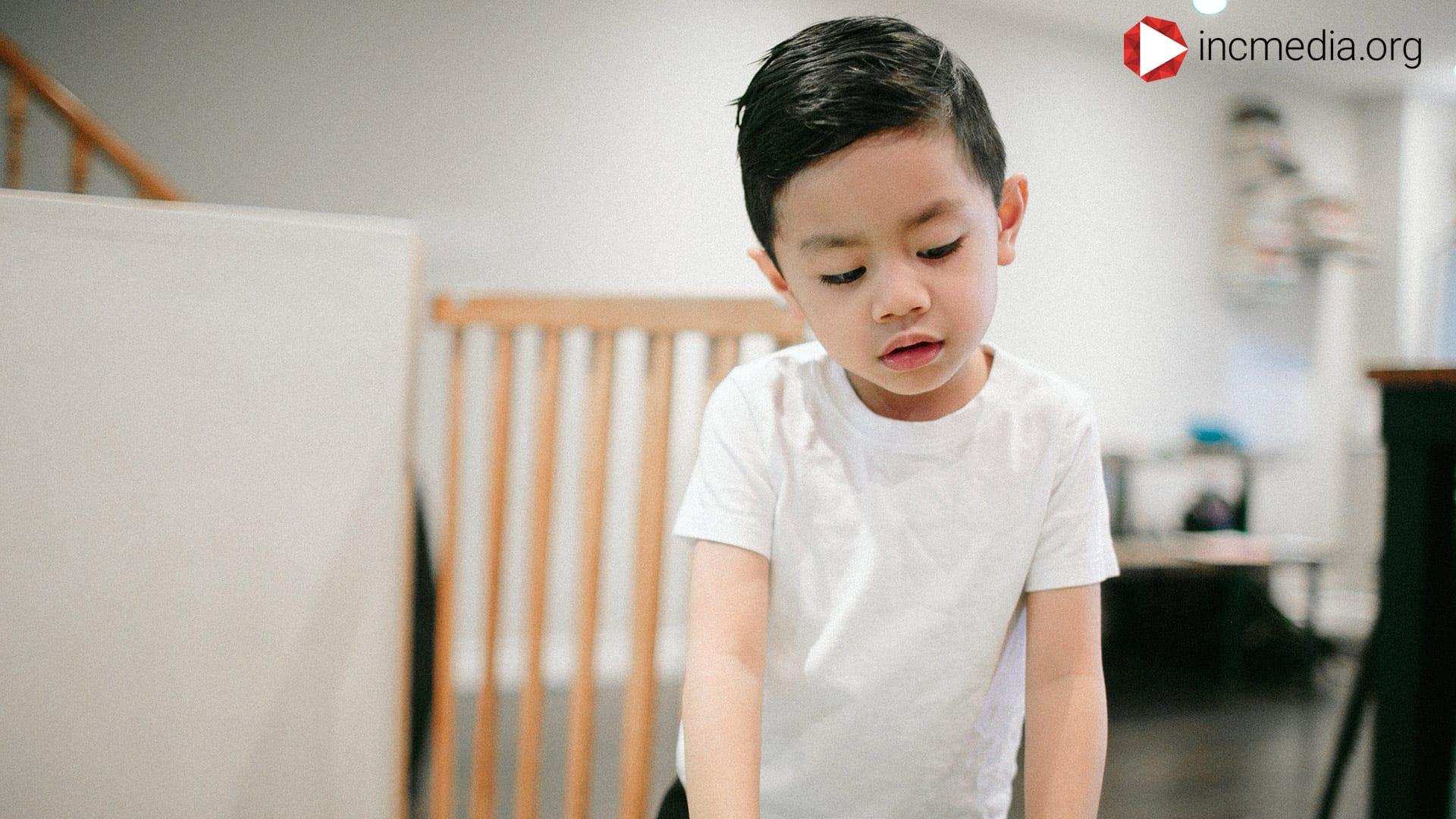 young boy looking down wearing a white shirt