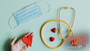 Hand holding paper cut out heart shape along with a face mask, stethoscope and heart-shaped candies laid out.