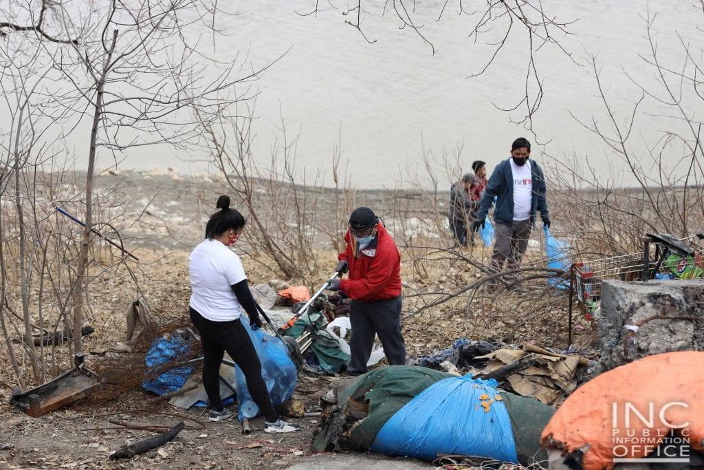 volunteers cleaning and gathering debris and garbage