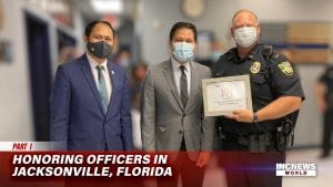 Two men in suits and masks pose with a police officer holding a certificate.