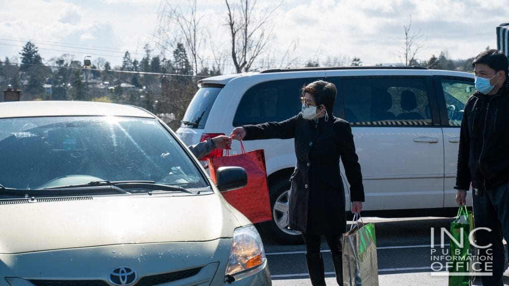 Iglesia Ni Cristo (INC) or Church Of Christ volunteers in Victoria, Canada approach frontline workers driving through to receive their care packages during the Aid To Humanity event.