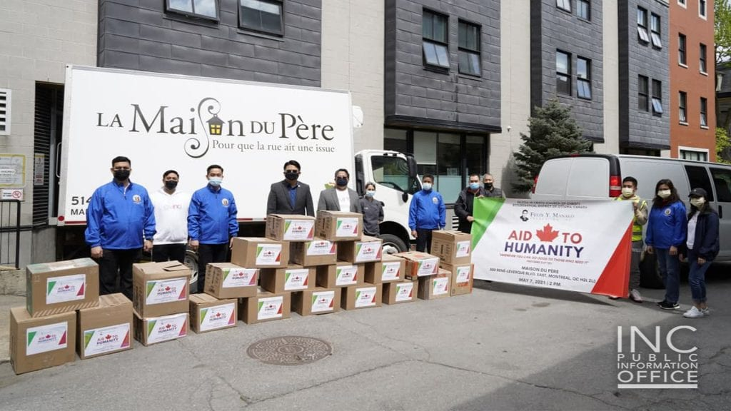 Happy group picture of Iglesia Ni Cristo (Church Of Christ) members with Sandra Auger from homeless shelter of La Maison du Père in Quebec, Canada, on sunny day after the volunteers had dropped off boxes which are part of the ten thousand pounds in donations that was delivered to seven charities in Canada from May 5 to May 7, 2021.