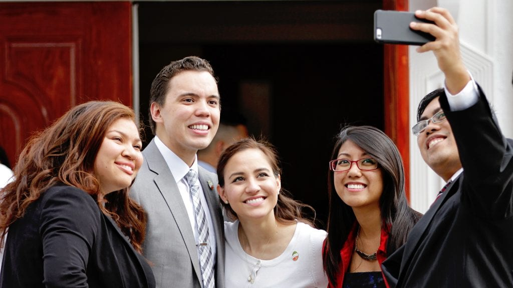 A group of people smiling for a selfie.