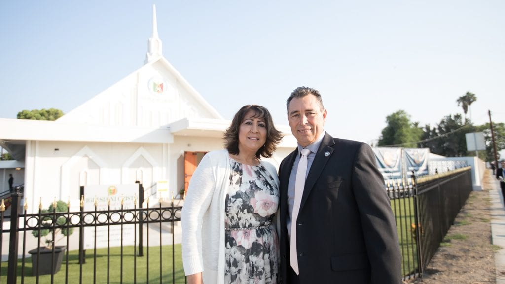 A couple smiling and standing in front of a house of worship.