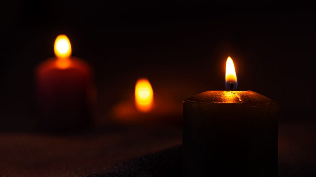 Three candles glowing in a dark room.
