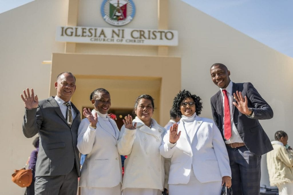 A group of people standing and waving in front of a Iglesia Ni Cristo building.